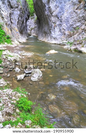 Small stream of water flows between tall limestone walls of a gorge  - stock photo