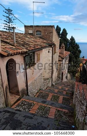 Small street in Sicilian town of Taormina descending toward the sea - stock photo
