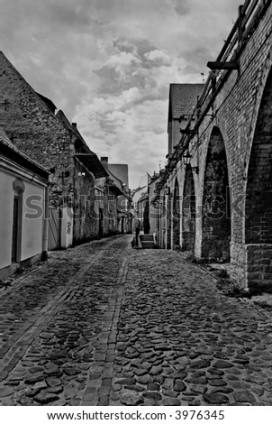 Small street in the old town (Riga, Latvia). Black and white photo - stock photo