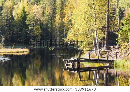 Small swimming bridge in a lake surrounded by colorful autumn forest - stock photo