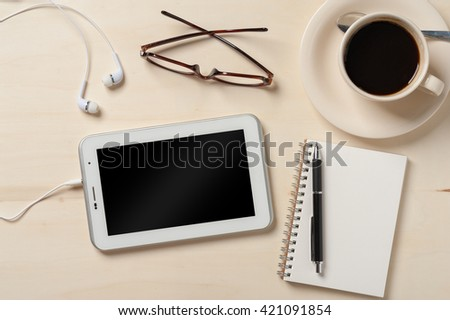 Small tablet pc with blank area on touchscreen with in ear headset,  notebook, pen,glasses, and coffee cup on wood table - stock photo