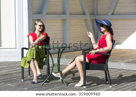 Small-talk between two aristocratic ladies in terrace - stock photo
