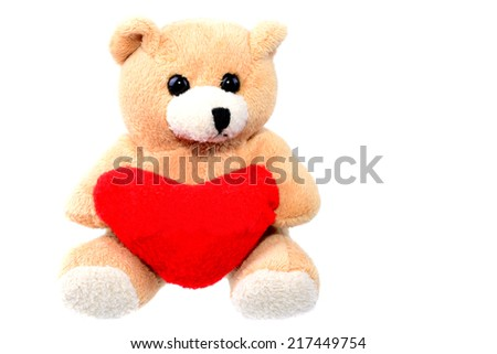 Small teddy bear holding a red heart isolated on white with copy space - stock photo