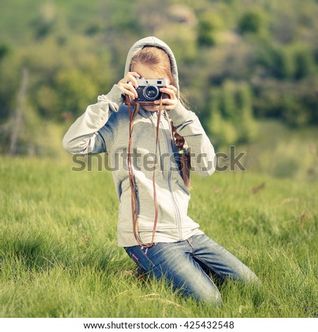 Small teenage girl taking photo with old camera at outdoors. Teenager girl learning photography with retro film camera  - stock photo