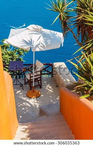 Small terrace of an apartment with umbrella, desk and chair in Oia town, Santorini island, Greece