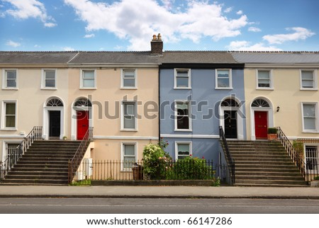 small three-story house stands beside road. doors, windows, stairs - stock photo