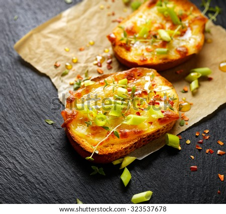 Small toast with melted cheese, scallions, chili peppers and fresh thyme - stock photo