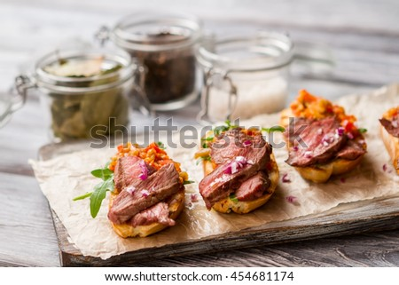 Small toasts with meat. Herb and mixture of vegetables. Simple dish from italian cuisine. Bruschetta cooked at home. - stock photo