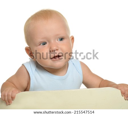Small toddler boy in playpen on a white background