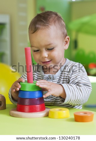 Small toddler or a baby child playing with puzzle circle shapes on a low table in a colorful children room in a nursery or preschool. - stock photo