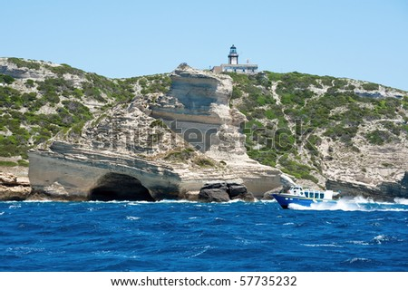 small tourist boat on sea with Pertusato lighthouse in the background, Corsica - France - stock photo