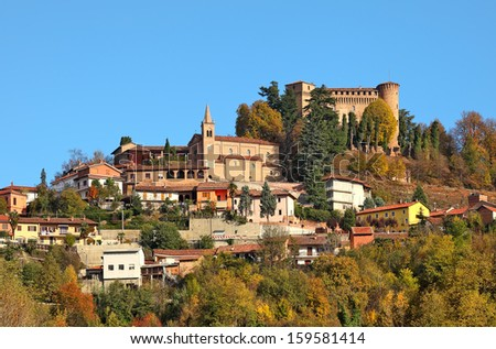 Small town and medieval castle among autumnal trees on top of the hill in Piedmont, Northern Italy. - stock photo