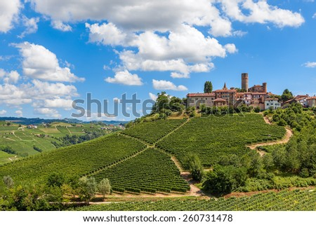 Small town on the hill with green vineyards under blue sky with white clouds in Piedmont, Northern Italy. - stock photo
