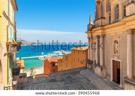 Small town square between old church and colorful houses with view on Mediterranean sea in Menton, France.
