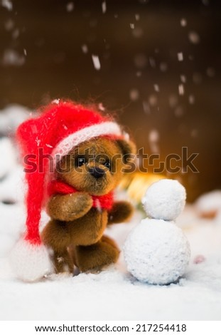 Small toy bear making snowman in christmas still life