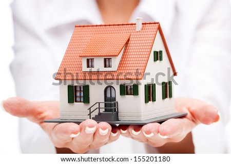 Small toy house in hands - stock photo