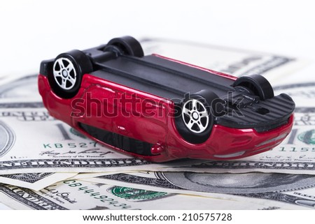 Small, toy, red car had accident on one hundred dollar banknotes, isolated on white background. - stock photo