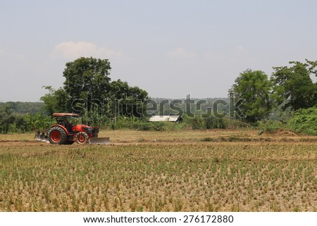 Small tractors are currently plough soil page. - stock photo