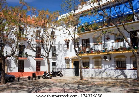 Small tranquil square surrounded by traditional apartment houses in the Old Town of Marbella in southern Spain, Anadalusia region - stock photo