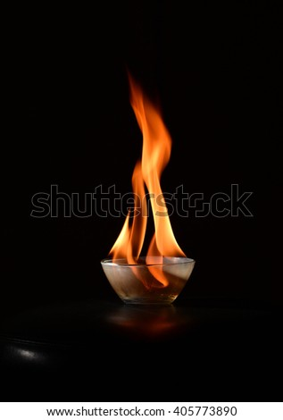 Small transparent glass bowl standing on a black surface with fire blazing in it close up isolated on black background - stock photo