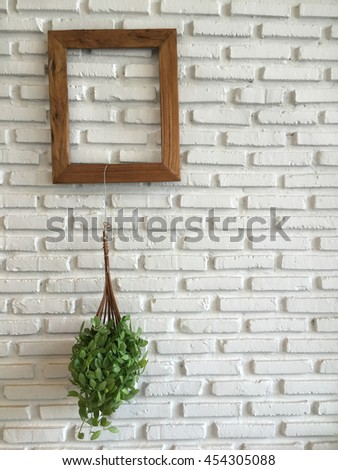 small tree hanging on wood frame with white brick background concept decor - stock photo