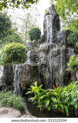 Small tropical garden waterfall - stock photo