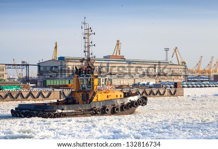 Small tug boat goes on icy channel in harbor of St.Petersburg cargo port