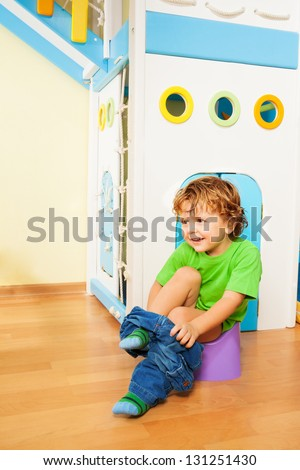 Small two years old boy putting off his pants as he learns to use a potty