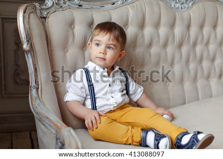 Small very cute boy in yellow pants and suspenders sitting on a chair and looks into the distance