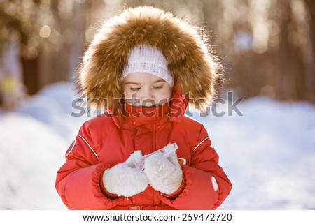 Small very cute girl in a red suit with fur hood holding an icicle in winter on the background of snowy sunset forest, close up - stock photo