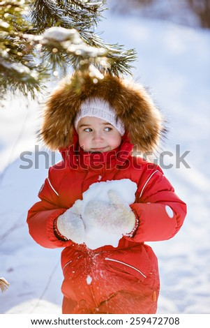 Small very cute girl in a red suit with fur hood keeps the snow in the hands of a winter forest background - stock photo
