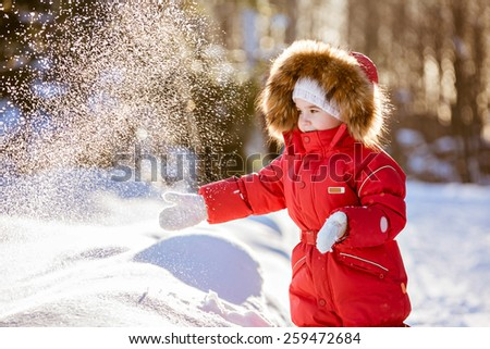 Small very cute girl in a red suit with fur hood throws snow in winter on the background of the sunset forest - stock photo