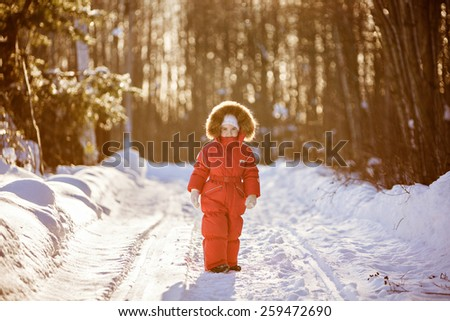 Small very cute girl in a red suit with fur hood winter amid the snowy forest sunset - stock photo