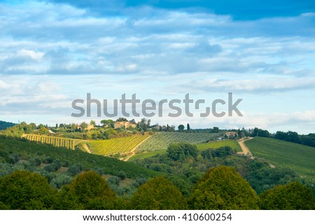 Small village on ridge above vineyards and olive groves and forest under cloudy skies