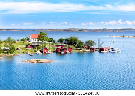 Small village with red buildings in Finnish archipelago on a sunny day - stock photo