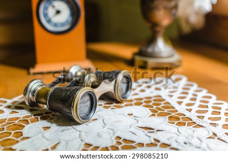 Small vintage binocular laying on the wooden table with an old clock