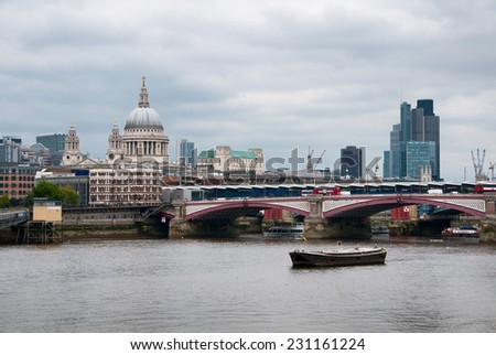Small Vintage Fishing Boat Passing Arch Bridge at Famous River Thames in London, with St Paul Cathedral View Afar. - stock photo