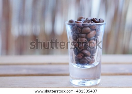 Small vodka glass full of coffee beans