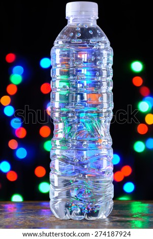 Small water bottle over bokeh light background
