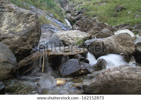 Small waterfall and big stones in mountain river