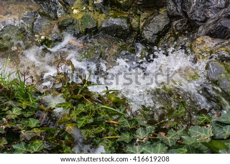 Small waterfall, cascade flowing over mossy boulders in a botanical garden. - stock photo