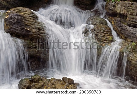 Small waterfall in a mountain forest in the morning.