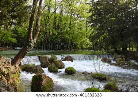 Small waterfall in green summer park - stock photo