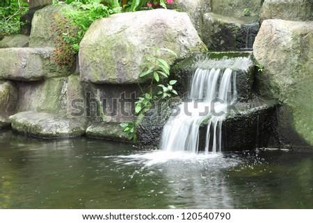 Small waterfall in public tropical garden. - stock photo