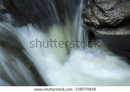 Small waterfall in the Sugar River, Newport, New Hampshire, with rocks and silky turbulence, closeup.
