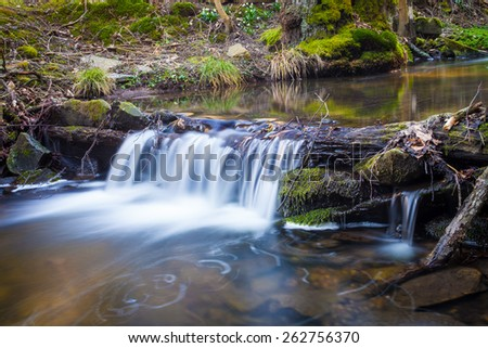 Small waterfall on creek flowing over the rocks and wood - stock photo