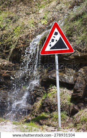 Small waterfall running behind a landslide sign outdoors - stock photo