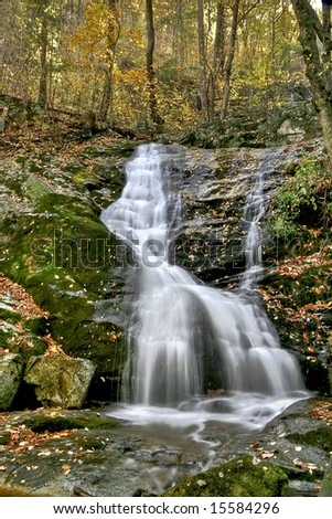 Small waterfall viewed in mid autumn along hiking trail. - stock photo