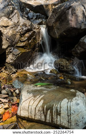 Small waterfall with natural light in deep forest.