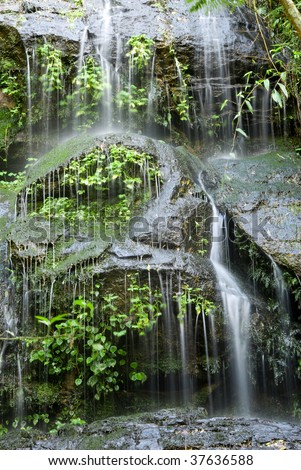 Small waterfall with rocks and plants. - stock photo